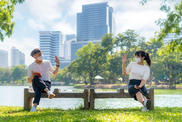아시아의 젊은 남녀가 인사하고 인사하고 6 피트 거리의 마스크 앉아 거리가 covid-19 바이러스로부터 보호하여 감염 위험에 대한 사회적 거리를 두십시오.