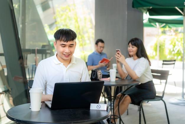 6 피트 거리의 거리에 대해 한 테이블에 한 사람당 앉아있는 아시아 젊은 남자와 여자는 커피 카페에서 감염 위험에 대한 사회적 소란을 위해 covid-19 바이러스로부터 보호합니다.