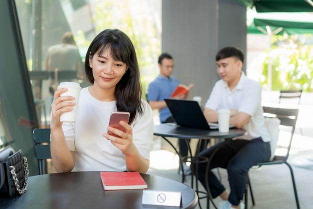 6 피트 거리의 거리에 대해 한 테이블에 한 사람당 앉아있는 아시아 젊은 남자와 여자는 커피 카페에서 감염 위험에 대한 사회적 소란을 위해 Covid-19 바이러스로부터 보호합니다. 프리미엄 사진