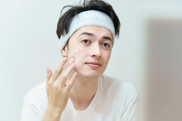 彼の顔にクリームを適用するアジアの若い男