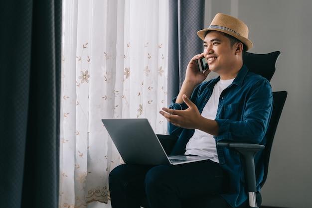 ノートパソコンと携帯電話で話し、笑顔で家にいるアジアの若い男。家に座って携帯電話を使用している男性。幸せなリラックスした座って、携帯電話でソーシャルメディアとチャット。