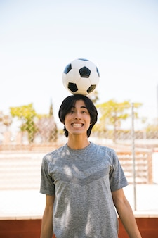 Asian young man balancing soccer ball on head