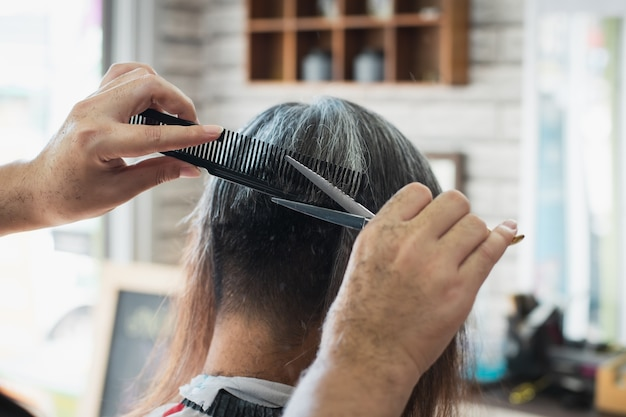 Asian young man being cut from long hair to short hair with scissor by professional barber in barbershop.