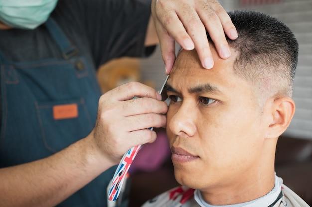 Азиатский молодой человек стригся бритвой профессиональным парикмахером в парикмахерской.