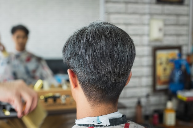 Asian young man being haircut with scissor by professional barber in barbershop. hairdresser using comb and scissors cut hair.