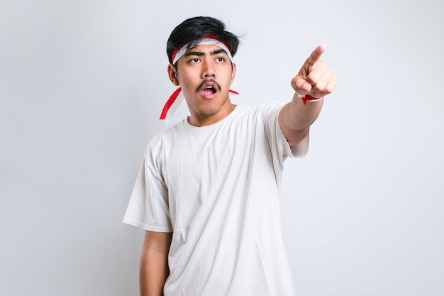 Asian young man in casual shirt pointing forward, looking at camera, make choosing you gesture against white background