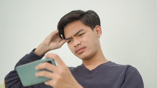 Азиатский молодой человек смущен игрой дома
