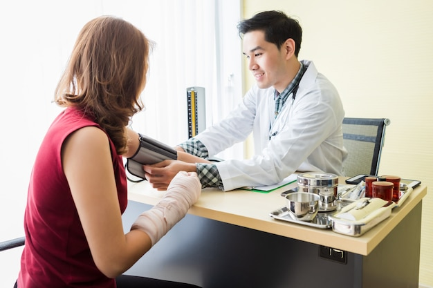 Asian young man doctor with measuring the pressure to the arm of a female patient wear arm splint with analogue pressure gauge for better healing in the room hospital.