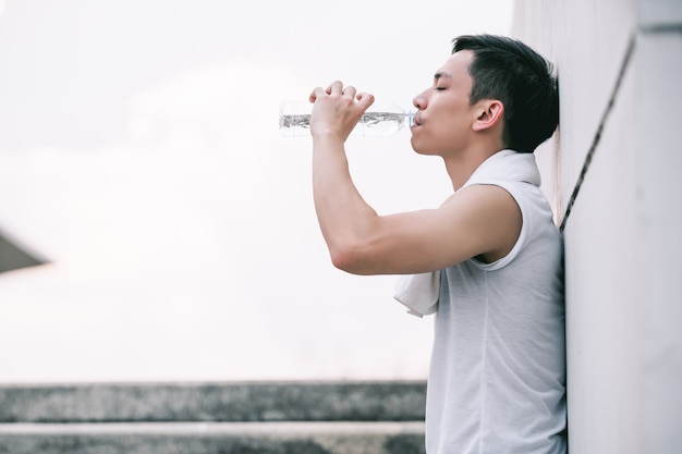 Asian young man drinking water after jogging