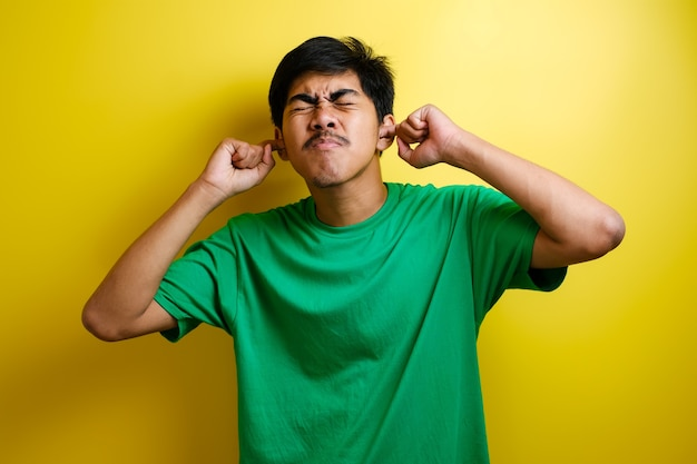 Asian young man in green t-shirt close his ears with both hands against yellow background