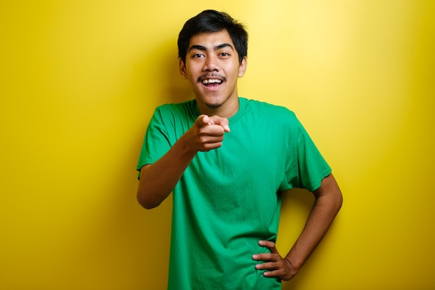 Asian young man in green t-shirt pointing forward, looking at camera, make choosing you gesture against yellow background