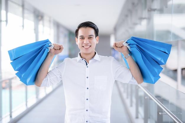 Asian young man holding shopping bags
