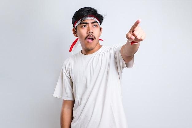 캐주얼 셔츠를 입은 아시아 젊은이가 앞을 가리키며 카메라를 바라보며 흰색 배경에 대해 제스처를 선택합니다.
