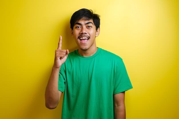 녹색 티셔츠를 입은 아시아 젊은이는 행복한 생각을 하고 위를 올려다보며 좋은 생각을 하고 있습니다. 복사 공간이 있는 노란색 배경의 반신 초상화