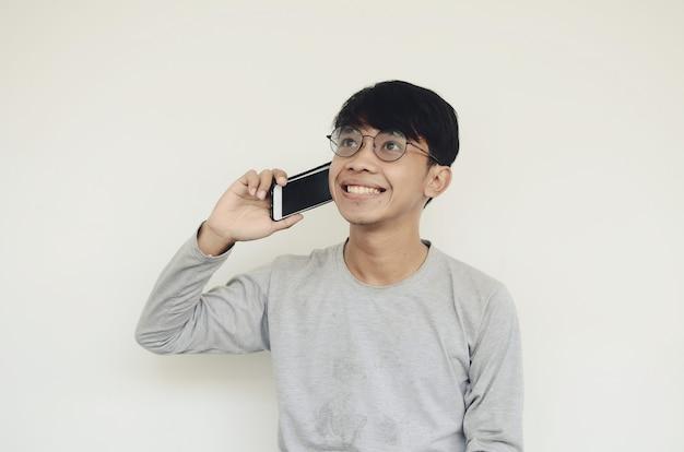 아시아 청년이 행복한 표정으로 친구에게 전화를 걸고 있다