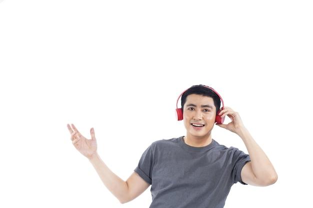 彼の携帯電話で音楽を聞いているアジアの若い男