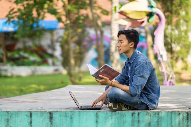 Азиатский молодой человек ищет идеи на своем ноутбуке и пишет в своей книге