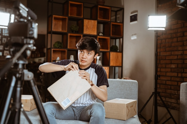 Asian young man making unboxing review recording video for vlog