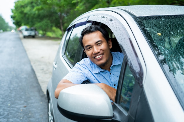 Asian young man opens window and smiles