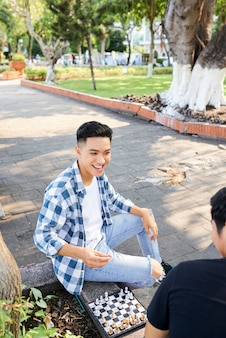 Азиатский молодой человек играет в шахматы вместе со своим другом на улице