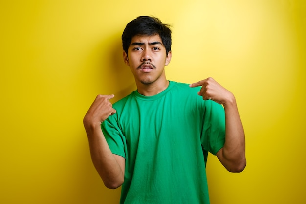 Asian young man pointing at himself wow shock reaction isolated over yellow color background