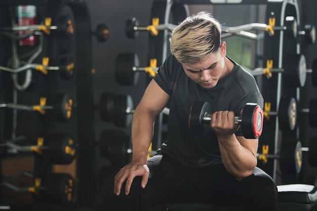 Азиатский молодой человек практикует тренировки с отягощениями в тренажерном зале, бодибилдинг. концепция задачи построения мышц. сильный спортсмен поднимает гантели крупным планом с копией пространства.