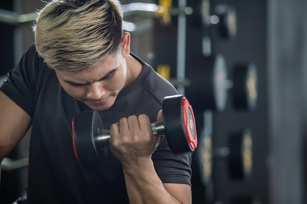 アジアの若い男性は、ジムでウェイトトレーニングトレーニング、ボディービルの練習を練習します。筋肉増強チャレンジコンセプト。強いスポーツマンは、コピースペースでダンベルをクローズアップします。