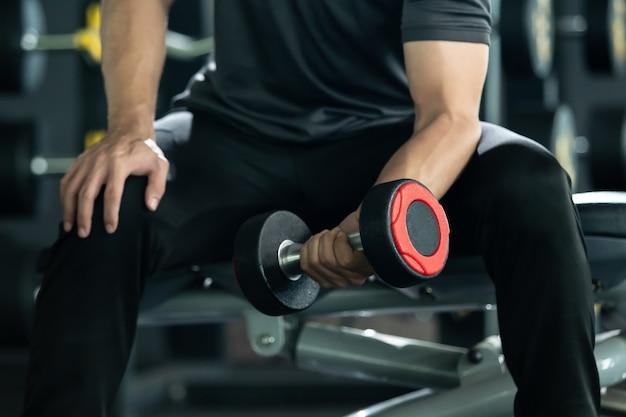 Азиатский молодой человек практикует тренировку с отягощениями в тренажерном зале, бодибилдинг. концепция задачи построения мышц. сильный спортсмен поднимает гантели крупным планом с copyspace.