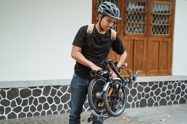 アジアの若い男が彼女の折りたたみ自転車を準備