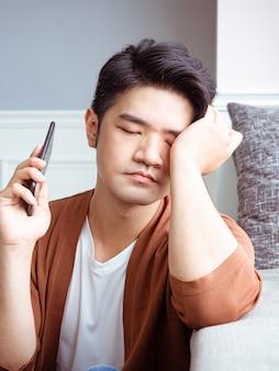 Азиатский молодой человек, протирая усталые глаза своим смартфоном.