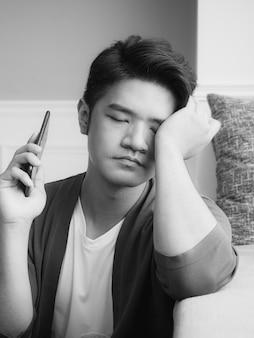 Азиатский молодой человек протирает усталые глаза своим смартфоном