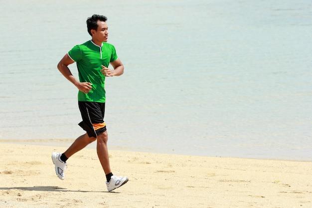 ビーチを走るアジアの若い男