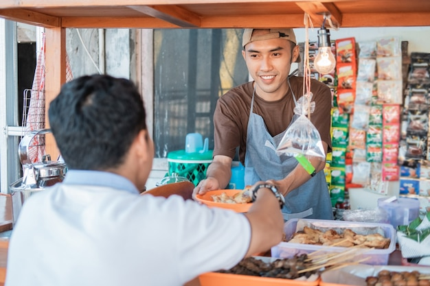 Азиатский молодой человек продавец в магазине тележек улыбается, обслуживая клиентов в киоске тележки