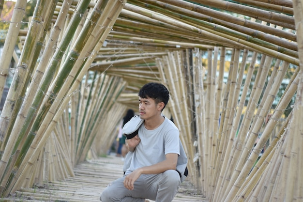 Asian young man sitting in a bamboo arch.