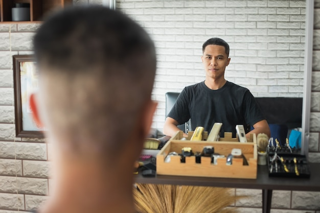 Asian young man sitting on chair and looking himself in mirror after finished haircut in barbershop.