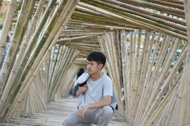 대나무 아치에 앉아 아시아 젊은이.