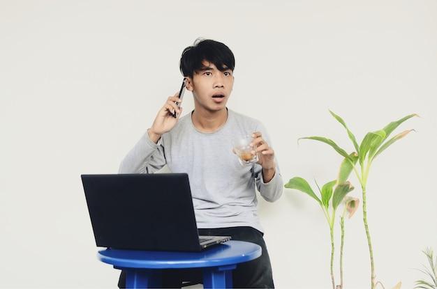 電話をかけるのに忙しいラップトップの前に座っているアジアの若い男