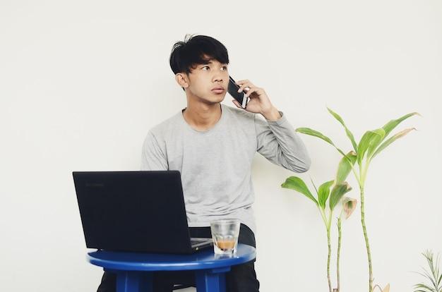 노트북 앞에 앉아 혼란스러운 얼굴로 전화하는 아시아 청년