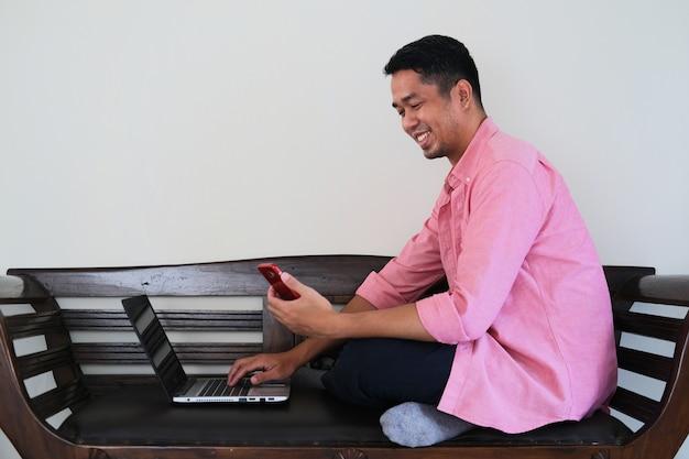 그의 노트북과 휴대 전화를 사용하여 작업하는 동안 나무 소파에 앉아 아시아 젊은 남자