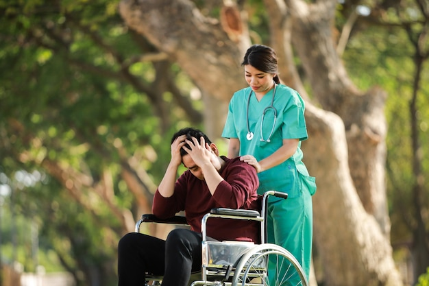 Asian young man sitting on the wheelchair in the park hospital