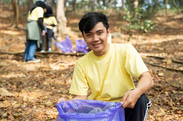 Волонтер азиатского молодого человека усмехаясь держа мешок для мусора