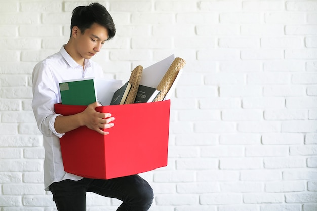 Asian young man student with books in hands
