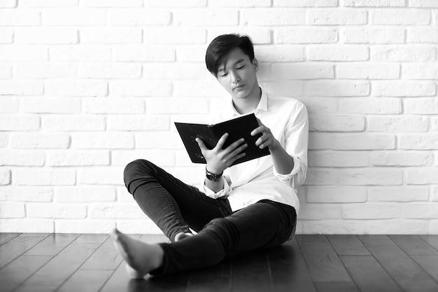 Азиатский молодой человек студент с книгами в руках