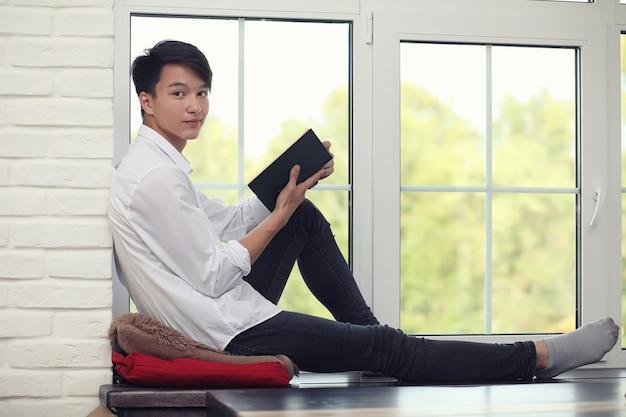 손에 책을 들고 아시아 젊은 남자 학생