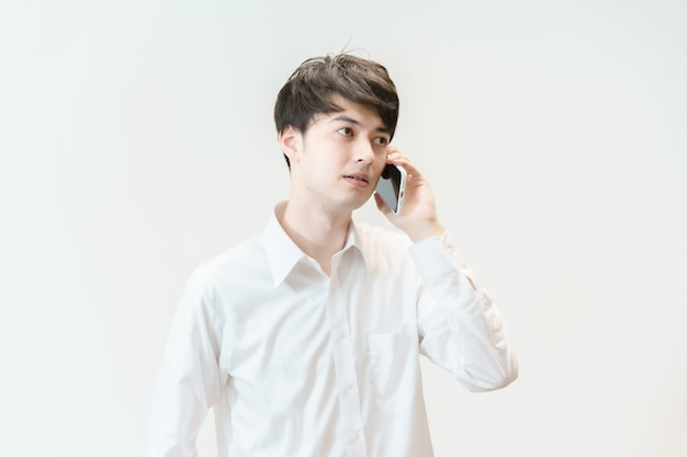 Азиатский молодой человек разговаривает по смартфону