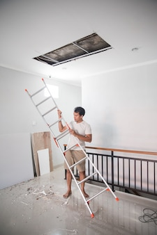 집에서 깨진 천장을 수리하기 위해 사다리를 사용하는 아시아 젊은이