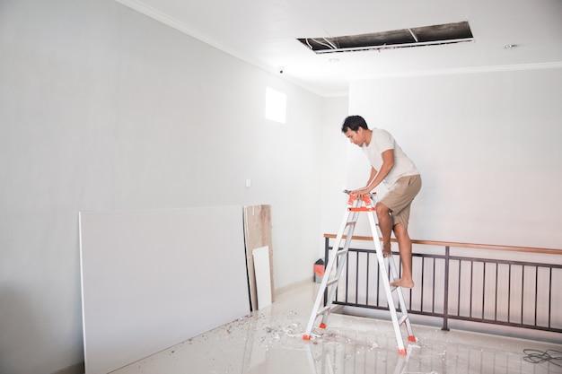 Азиатский молодой человек с помощью лестницы отремонтирует сломанный потолок дома