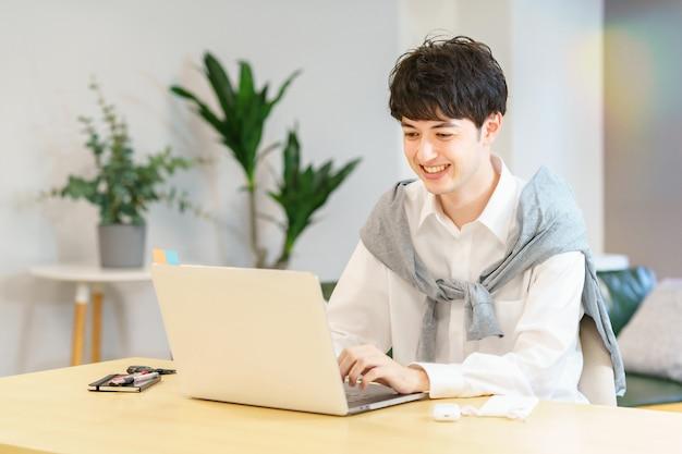 캐주얼한 방에서 노트북을 사용하는 아시아 청년