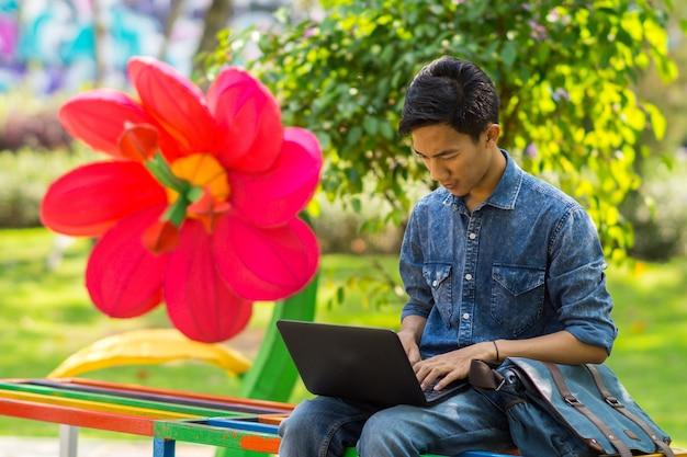 Азиатский молодой человек с помощью компьютера на открытом воздухе