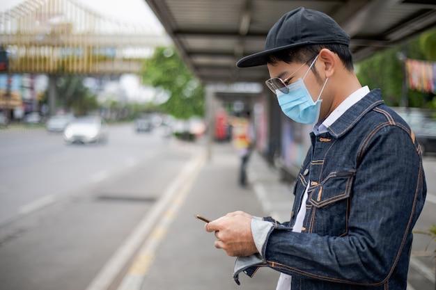Азиатский молодой человек, используя смартфон в городе и носить маску для защиты от загрязнения воздуха, твердых частиц и для защиты от вируса гриппа, гриппа, коронавируса